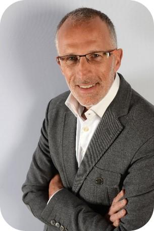 Portarit pris de trois quart d'Yves Salaun vêtu d'une chemise blanche et d'une veste grise